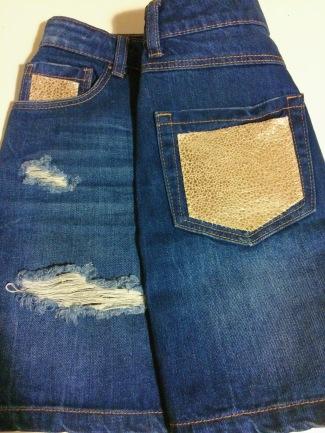 Falda customizada en bolsillo trasero y delantero, con piel en tonos dorado.